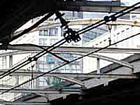 Gazing at the cables over the platform in South Gate of Shinjuku station surrounded by high-rise buildings.